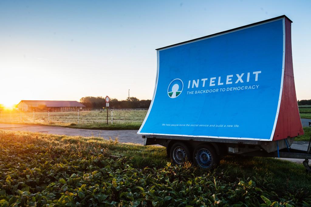 """Plakat INTELEXIT in der Nähe des """"Dagger-Komplex"""" bei Darmstadt. Im Hintergrund ist eine Antennenanlage der US-Einrichtung zu sehen."""