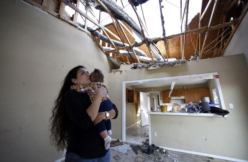 Lindsay Diaz and her son, 7-month-old Arian Krasniqui, in the livingroom of their Rowlett home where they hunkered down in the bathtub for safety during the December tornadoes. They have bounced around from family homes to hotels waiting on a temporary rent house to open up. Photographed Friday, February 19, 2016. (photo copyright Lara Solt)