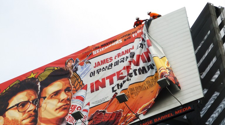 "Billboard for ""The Interview"" being taken down after being hacked (Courtesy of Radio Free Asia)"