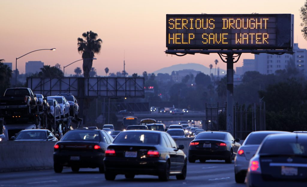 """Morning traffic makes it's way toward downtown Los Angeles along the Hollywood Freeway past an electronic sign warning of severe drought on Friday, Feb. 14, 2014. California is taking to the highways to spread the word about water conservation after months of drought. This week the California Department of Transportation launched an education campaign with 700 electronic highway boards displaying the message: """"Serious Drought. Help Save Water."""" (AP Photo/Richard Vogel)"""
